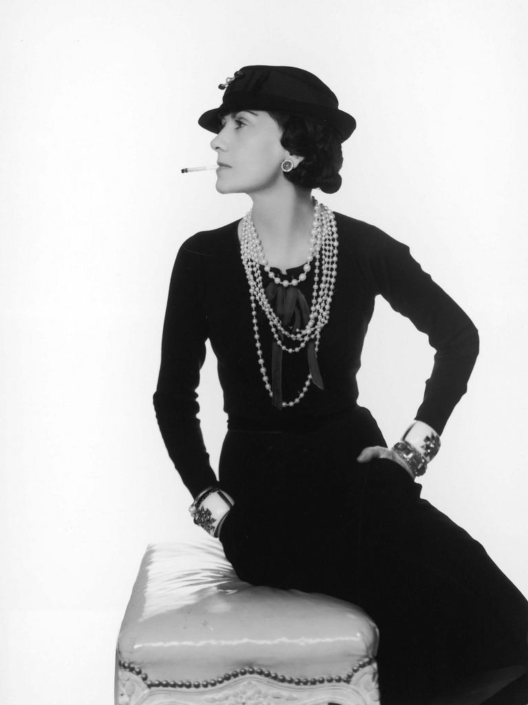 Coco Chanel in a classic pose – wearing a little black dress and a string of pearls.
